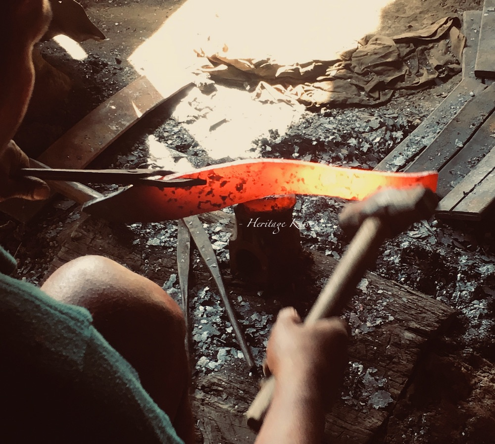 Forging high carbon steel to a kukri knife.